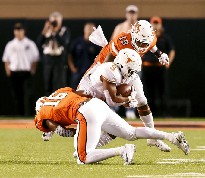 Texas running back Tre Watson (5) is brought down by Oklahoma State linebackers Devin Harper (16) and Justin Phillips (19) in the 2nd half of an NCAA college football game in Stillwater, Okla., Saturday, Oct. 27, 2018. Oklahoma State defeated Texas 38-35. (AP Photo/Brody Schmidt)