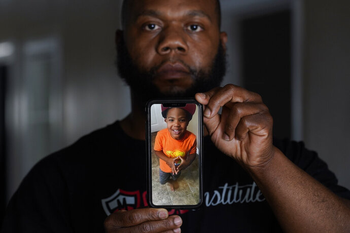 Leon Abdullah El-Alamin shows a photo of his son Leon Jr., in Mt. Morris Township, Mich., Wednesday, Jan. 13, 2021.   (AP Photo/Paul Sancya)