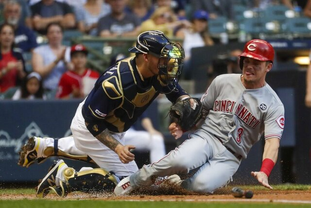 FILE - In this July 23, 2019, file photo, Milwaukee Brewers catcher Yasmani Grandal tags out Cincinnati Reds' Scooter Gennett at home during the first inning of a baseball game in Milwaukee. Grandal is among several free agents who signed with the Chicago White Sox. (AP Photo/Morry Gash, File)