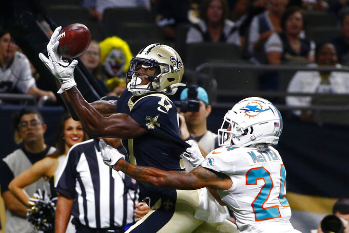 New Orleans Saints wide receiver Emmanuel Butler (17) pulls in a touchdown pass over Miami Dolphins cornerback Torry McTyer (24) in the first half of an NFL preseason football game in New Orleans, Thursday, Aug. 29, 2019. (AP Photo/Butch Dill)