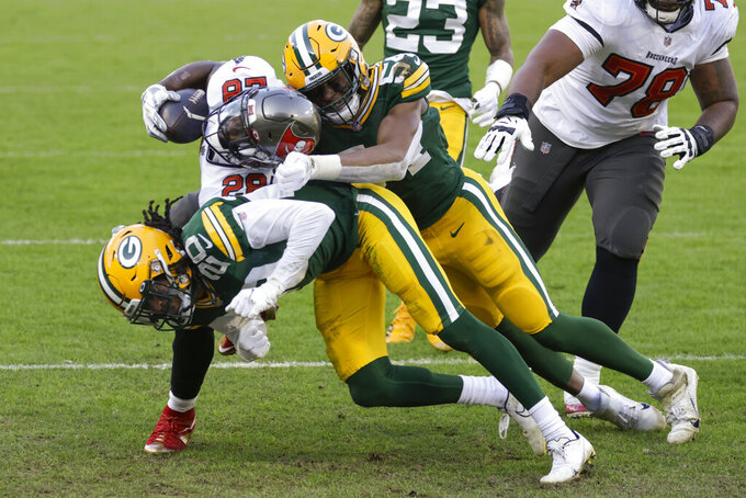 Tampa Bay Buccaneers' Leonard Fournette (28) powers past Green Pay Packers defenders to score on a 20-yard touchdown run during the first half of the NFC championship NFL football game in Green Bay, Wis., Sunday, Jan. 24, 2021. (AP Photo/Matt Ludtke)