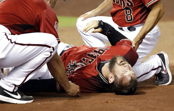 Arizona Diamondbacks' Steven Souza Jr. lies on the field after getting injured while scoring against the Chicago White Sox in the fourth inning of a spring training baseball game Monday, March 25, 2019, in Phoenix. (AP Photo/Elaine Thompson)