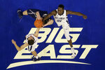 Xavier's Zach Hankins, center, competes for a rebound against Villanova's Collin Gillespie, left, and Dhamir Cosby-Roundtree during the first half of an NCAA college basketball game Friday, Jan. 18, 2019, in Philadelphia. (AP Photo/Matt Slocum)