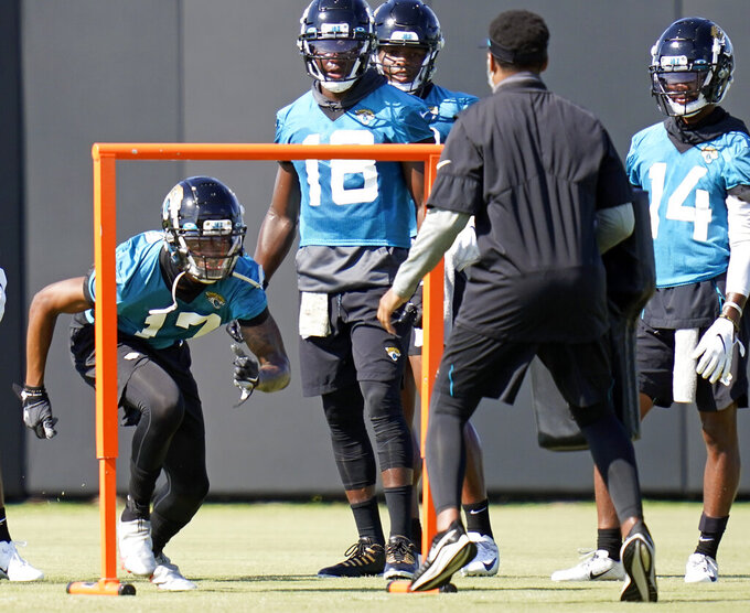 Jacksonville Jaguars wide receiver DJ Chark Jr., left, performs a drill as teammates Chris Conley (18) and Terry Godwin (14) look on during an NFL football workout, Thursday, Aug. 13, 2020, in Jacksonville, Fla. (AP Photo/John Raoux)