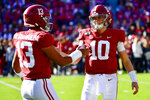 FILE - In this Nov. 9, 2019, file photo, Alabama quarterbacks Tua Tagovailoa (13) and Mac Jones (10) shake hands  before an NCAA football game against LSU in Tuscaloosa, Ala. The former Alabama teammates face each other when the Miami Dolphins and Tagovailoa, take on Jones and the New England Patriots on Sunday, Sept. 12, 2021, in Foxborough, Mass.  (AP Photo/Vasha Hunt, File)
