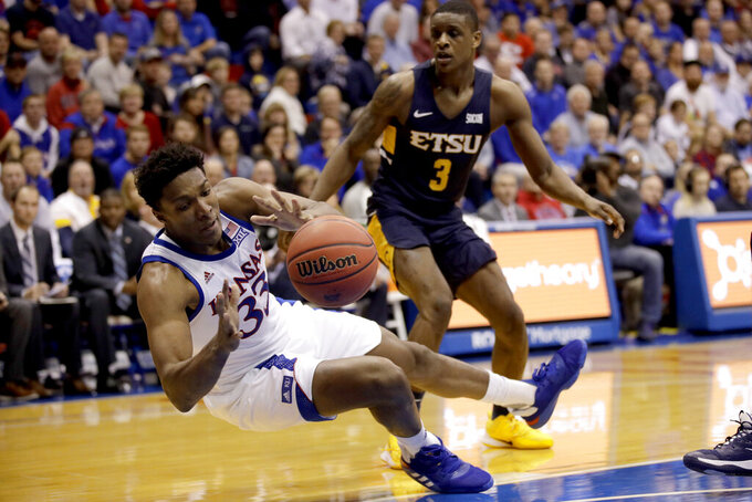 Kansas forward David McCormack (33) passes the ball as he falls during the first half of an NCAA college basketball game against East Tennessee State Tuesday, Nov. 19, 2019, in Lawrence, Kan. (AP Photo/Charlie Riedel)