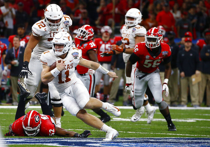 Texas quarterback Sam Ehlinger (11) carries past Georgia defensive lineman Tyler Clark (52) during the first half of the Sugar Bowl NCAA college football game in New Orleans, Tuesday, Jan. 1, 2019. (AP Photo/Butch Dill)