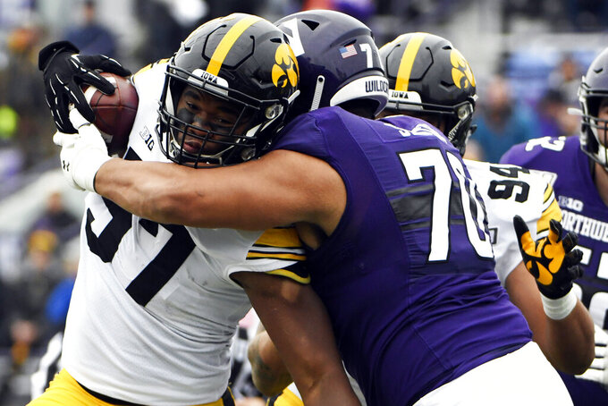 Iowa defensive end Chauncey Golston (57) intercepts a pass as Northwestern offensive lineman Rashawn Slater (70) tackles him during the first half of an NCAA college football game, Saturday, Oct. 26, 2019, in Evanston, Ill. (AP Photo/David Banks)