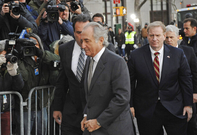 FILE - Bernard Madoff arrives at Manhattan federal court, Thursday, March 12, 2009, in New York.  Madoff, the financier who pleaded guilty to orchestrating the largest Ponzi scheme in history, died early Wednesday, April 14, 2021,  in a federal prison, a person familiar with the matter told The Associated Press.  (AP Photo/ Louis Lanzano, File)