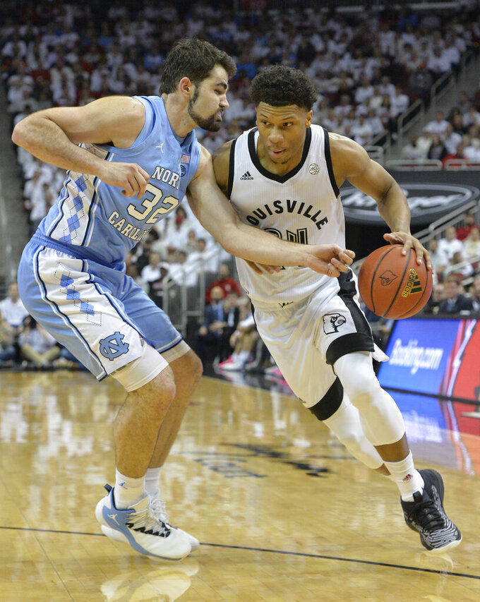 Louisville forward Dwayne Sutton (24) attempts to drive past the defense of North Carolina forward Luke Maye (32) during the second half of an NCAA college basketball game in Louisville, Ky., Saturday, Feb. 2, 2019. North Carolina won 79-69. (AP Photo/Timothy D. Easley)