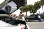 Renee Bracey loads a bag of food into a vehicle as she works with other volunteers at a food distribution for local residents sponsored by Feeding South Florida, Thursday, Jan. 28, 2021, in Florida City, Fla. (AP Photo/Lynne Sladky)