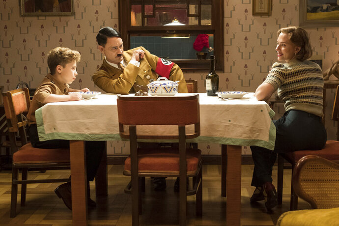 This image released by Fox Searchlight Pictures shows, from left, Roman Griffin Davis, Taika Waititi and Scarlett Johansson in a scene from the WWII satirical film