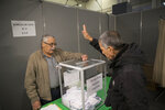 A Algerian voter casts his vote, Thursday, Dec.12, 2019, at the Algerian consulate in Marseille, southern France. Five candidates have their eyes on becoming the next president of Algeria in Thursday's contentious election boycotted by a massive pro-democracy movement. (AP Photo/Daniel Cole)