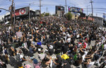 In this photo taken with a wide angle lens, demonstrators sit in an intersection during a protest over the death of George Floyd, Saturday, May 30, 2020, in Los Angeles. Protests were held in U.S. cities over the death of Floyd, a black man who died after being restrained by Minneapolis police officers on May 25. (AP Photo/Mark J. Terrill)