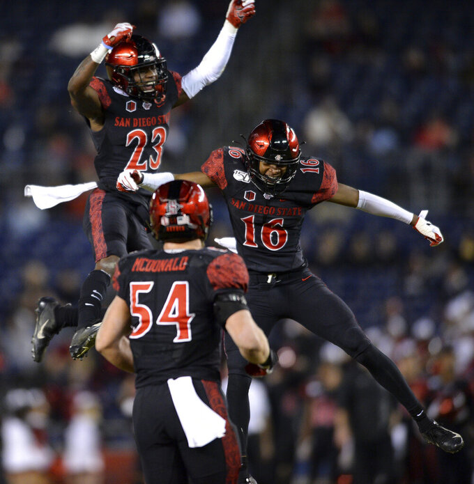 FILE - In this Nov. 15, 2019, file photo, San Diego State cornerbacks Darren Hall (23) and Luq Barcoo (16) celebrate after an interception by safety Tariq Thompson during the second half of the team's NCAA college football game against Fresno State. San Diego State and Central Michigan meet Saturday, Dec. 21, 2019, in the New Mexico Bowl in Albuquerque, N.M. in a game expected to be a defensive battle. (AP Photo/Orlando Ramirez,File)