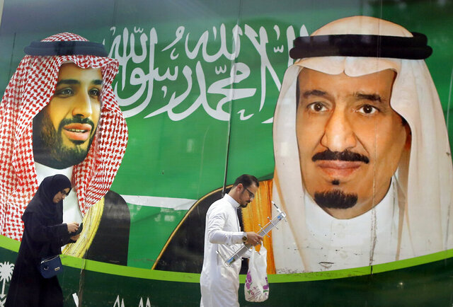 People walk past a banner showing Saudi King Salman, right, and his Crown Prince Mohammed bin Salman, outside a mall in Jiddah, Saudi Arabia, Saturday, March 7, 2020. (AP Photo/Amr Nabil)