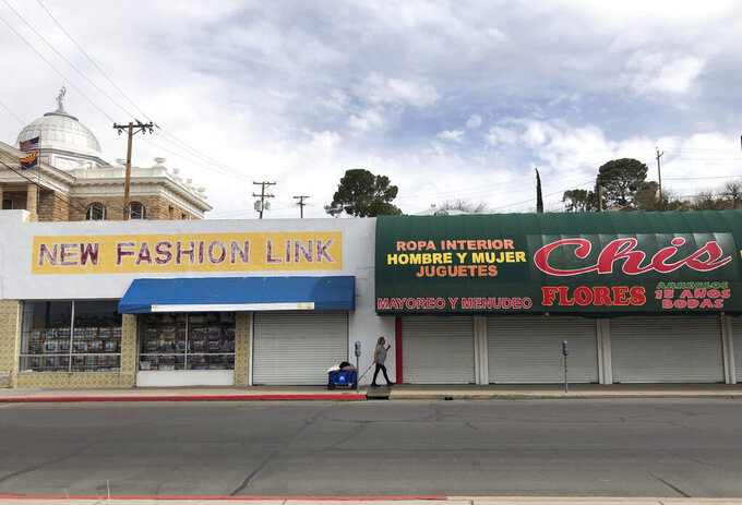 A woman walks past two out-of-business clothing stores located steps away from the U.S.-Mexico border on March 15, 2021 in Nogales, Ariz. The economic wear from nearly 12 months of a partially shut border is easy to spot in downtown Nogales. Bargain clothing stores, money exchanges, secondhand shops and retailers selling plastic knickknacks within walking distance of the border stand closed and many storefronts are boarded up. (AP Photo/Suman Naishadham)