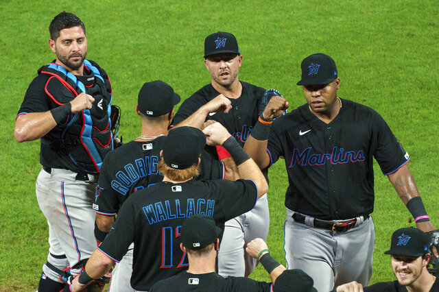 FILE - In this Friday, July 24, 2020, file photo, Miami Marlins' Jesus Aguilar, right, celebrates a win with teammates following a baseball game against the Philadelphia Phillies in Philadelphia. Marlins CEO Derek Jeter blames the team's coronavirus outbreak on a collective false sense of security that made players lax about social distancing and wearing masks. Infected were 21 members of the team's traveling party, including at least 18 players. (AP Photo/Chris Szagola, File)