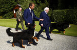 The dogs of Irish President Michael D. Higgins walk around him and French President Emmanuel Macron as they meet in Aras an Uachtarain, Dublin, Ireland, Thursday, Aug. 26, 2021. French President Emmanuel Macron is on Thursday on his first visit to Ireland, where talks are expected to focus on the situation in Afghanistan and European issues. (Clodagh Kilcoyne/Pool Photo via AP)