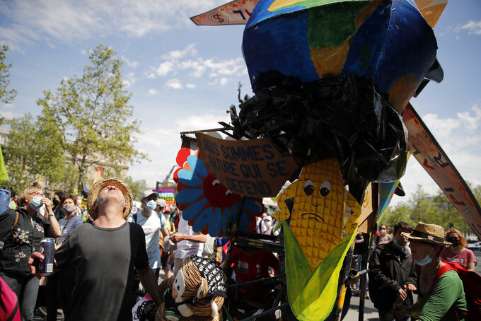 Demonstrators attend a rally against the climate change in Paris, Sunday, May 9, 2021. Thousands of French demonstrators took to the streets of Paris and other cities on Sunday to call for more ambitious measures to fight against climate change. (AP Photo/Christophe Ena)