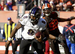 Baltimore Raven quarterback Lamar Jackson looks for running room as Cleveland Brown's Chad Thomas (92) follows the play during an NFL football game at FirstEnergy Stadium in Cleveland on Sunday, Dec. 22, 2019. (Warren Dillaway/The Star-Beacon via AP)