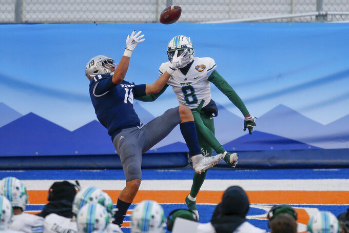 Nevada tight end Cole Turner (19) reaches for a pass for a touchdown, in the end zone next to Tulane cornerback Willie Langham (8) in during the second half of the Famous Idaho Potato Bowl NCAA college football game Tuesday, Dec. 22, 2020, in Boise, Idaho. Nevada won 38-27. (AP Photo/Steve Conner)