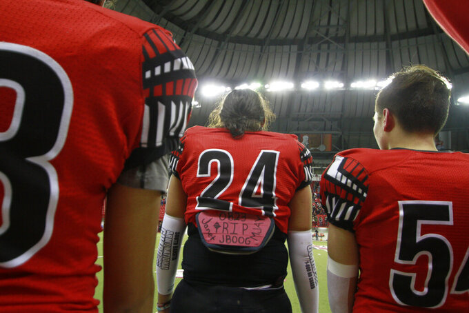 "In this Nov. 8, 2019 photo, Jayton Pease, (24) wear his late brother's nickname ""JBOOG"" on his back-plate pad to honor J'von Justice Shields, who killed himself in July, 2018 as Jayton prepares to play in the All Nations Conference championship game at ""The Dome"" in Vermillion, S.D.. He said his brother always dreamed of playing at ""The Dome"" where championship football games are decided. (AP Photo/Stephen Groves)"