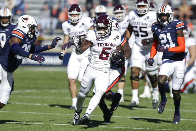 Texas A&M running back Devon Achane (6) carries the ball against Auburn during the first half of an NCAA college football game on Saturday, Dec. 5, 2020, in Auburn, Ala. (AP Photo/Butch Dill)