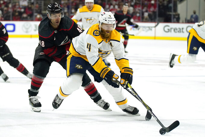 Carolina Hurricanes left wing Jordan Martinook (48) pursues as Nashville Predators defenseman Ryan Ellis (4) controls the puck during the second period in Game 1 of an NHL hockey Stanley Cup first-round playoff series in Raleigh, N.C., Monday, May 17, 2021. (AP Photo/Gerry Broome)