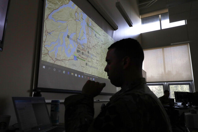 In this Tuesday, March 31, 2020, photo, Washington National Guard Spc. Spencer Graves works in front of a map, at Camp Murray, Wash., showing locations of area food banks in Washington state. Guard soldiers are expected to deploy later in the week to assist with food bank operations as part of their first mission related to the outbreak of the new coronavirus. (AP Photo/Ted S. Warren)