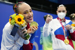 Vlada Chigereva, member of team of Russian Olympic Committee poses with gold medal after artistic swimming team free routine competition at the 2020 Summer Olympics, Saturday, Aug. 7, 2021, in Tokyo, Japan. (AP Photo/Dmitri Lovetsky)