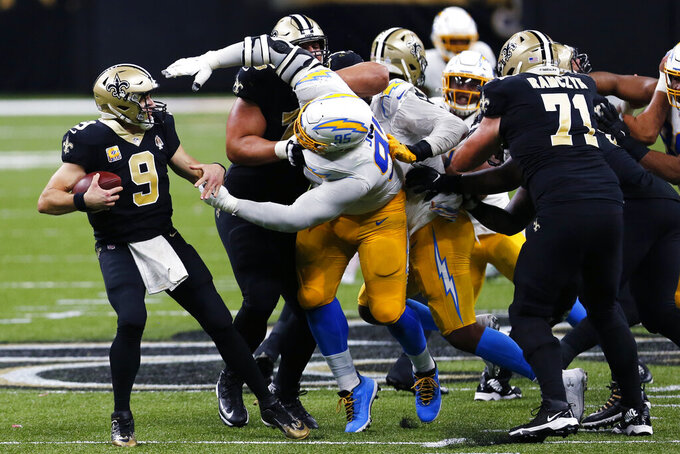 New Orleans Saints quarterback Drew Brees (9) tries to avoid the sack by Los Angeles Chargers defensive tackle Linval Joseph (95) in the second half of an NFL football game in New Orleans, Monday, Oct. 12, 2020. (AP Photo/Brett Duke)