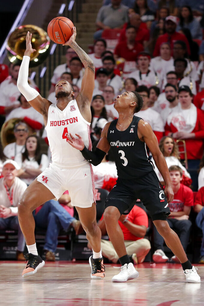 Houston forward Justin Gorham (4) reaches for the ball after it is knocked away by Cincinnati guard Mika Adams-Woods (3) during the first half of an NCAA college basketball game Sunday, March 1, 2020, in Houston. (AP Photo/Michael Wyke)