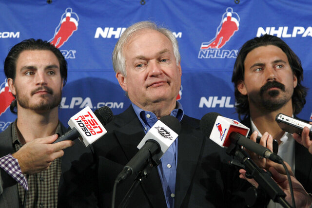 FILE - In this Sept. 12, 2012, file photo, National Hockey League Players' Association executive director Donald Fehr, center, is joined by players George Parros , left, and Kevin Westgath after meeting with NHL officials in New York. The NHL is rapidly approaching the finish line of completing the season and awarding the Stanley Cup after holding an expanded playoff in quarantined bubbles. Do not expect bubbles to be an option for the 2020-21 season. Fehr said exactly replicating the playoff quarantine environment is not something players are interested in doing for an entire season. (AP Photo/Mary Altaffer, File)