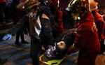 A woman injured in clashes with the police during a protest against President Evo Morales' reelection, is carried to safety, in La Paz, Bolivia, Thursday, Nov. 7, 2019. The United Nations on Thursday urged Bolivia's government and opposition to restore
