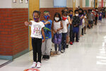 This Sept. 8, 2021 photo shows kindergarten students at Booker T. Washington Community Elementary School in Las Cruces, N.M., lining up on their way to lunch. They put their arms straight out to help keep social distance between the person in front of them. (Miranda Cyr/Las Cruces Sun-News via AP)