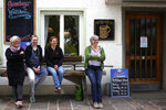 In this photo taken Friday, May 1, 2020 brewery daughters Birgit Detter, left, Iris Detter, second right, Sabine Detter, right, and waitress Elisabeth Haeckl rest in front of the 120 year old family brewery and traditional Bavarian restaurant in Altoetting, Germany. The 'Graminger Weissbraeu' brewery, which has been in the same family for a century, is preparing to welcome guests back to its restaurant for the first time in two months — with new rules and fears for the future. (AP Photo/Matthias Schrader)