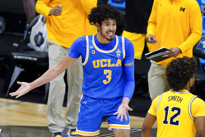 UCLA guard Johnny Juzang (3) questions a call during the first half of an Elite 8 game against Michigan in the NCAA men's college basketball tournament at Lucas Oil Stadium, Tuesday, March 30, 2021, in Indianapolis. (AP Photo/Darron Cummings)