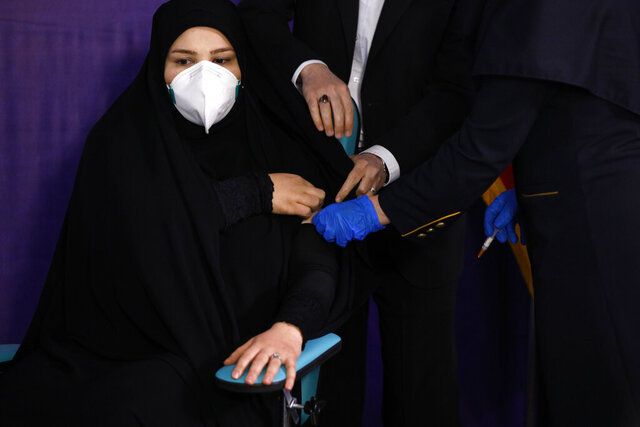 Tayebeh Mokhber is injected with the Coviran coronavirus vaccine produced by Shifa Pharmed, part of a state-owned pharmaceutical conglomerate, in a ceremony in Tehran, Iran, Tuesday, Dec. 29, 2020. The first study of the safety and effectiveness of the coronavirus vaccine in Iran began Tuesday, state TV reported, with dozens due to receive the domestically developed shot in the hardest-hit country in the Middle East. (AP Photo/Aref Taherkenareh)