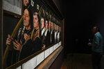 """A person looks at Jan van Scorel's Twelve Members of the Haarlem Brotherhood of Jerusalem Pilgrims, painted around 1528, during a press preview of the Remember Me exhibit which brings together international masterpieces of portraiture at the Rijksmuseum in Amsterdam, Netherlands, Tuesday, Sept. 28, 2021. As COVID-19 lockdowns ease and borders reopen, there is a gathering at Amsterdam's Rijksmuseum of people from around Europe, depicted in more than 100 Renaissance portraits. The Dutch national museum's new exhibition """"Remember Me,"""" covers the century 1470-1570. (AP Photo/Peter Dejong)"""