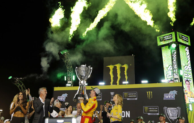 Joey Logano, second from right, holds the trophy with Steve Phelps, president of NASCAR after winning the Cup Series Championship auto race at the Homestead-Miami Speedway, Sunday, Nov. 18, 2018, in Homestead, Fla. (AP Photo/Terry Renna)