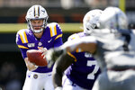 LSU quarterback Joe Burrow, left, takes a snap in the first half of an NCAA college football game against Vanderbilt Saturday, Sept. 21, 2019, in Nashville, Tenn. (AP Photo/Mark Humphrey)