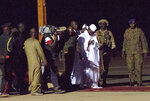 FILE - In this file photo dated Saturday Jan. 21, 2017, Gambia's defeated leader Yahya Jammeh, wearing white, departs at Banjul airport.  Gambia's longtime dictator Yahya Jammeh, who fled into exile three years ago after an election loss, says he wants to return home, according to an audio recording released by his political party Tuesday Jan. 14, 2020.(AP Photo/Jerome Delay, FILE)