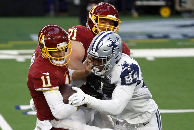 Washington Football Team quarterback Alex Smith (11) is sacked by Dallas Cowboys defensive end Randy Gregory (94) as guard Wes Schweitzer (71) helps on the play in the first half of an NFL football game in Arlington, Texas, Thursday, Nov. 26, 2020. (AP Photo/Roger Steinman)