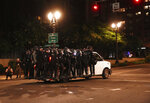 Portland Police line around a van and drive away from protesters rallying at the Mark O. Hatfield United States Courthouse on Saturday, Sept. 26, 2020, in Portland, Ore. (AP Photo/Allison Dinner)
