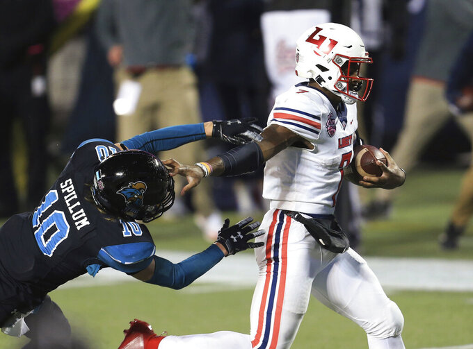 Liberty quarterback Malik Willis (7) runs for a touchdown past Coastal Carolina safety Alex Spillum (10) during the second half of the Cure Bowl NCAA college football game Saturday, Dec. 26, 2020, in Orlando, Fla. (AP Photo/Matt Stamey)