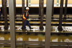 A worker surveys the flooded Lincoln Center subway station, in New York, Monday, Jan. 13, 2020. A water main break flooded streets on Manhattan's Upper West Side near Lincoln Center and hampered subway service during the Monday morning rush hour. (AP Photo/Richard Drew)