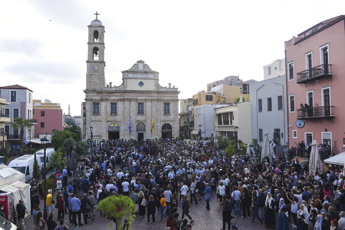 """People gather outside the Metropolitan church ahead of the funeral service for the late Greek composer Mikis Theodorakis, in Chania, Crete island, Greece, Thursday, Sept. 9 2021. Theodorakis died Thursday, Sept. 2, 2021 at 96. He penned a wide range of work, from somber symphonies to popular TV and film scores, including for """"Serpico"""" and """"Zorba the Greek."""" He is also remembered for his opposition to the military junta that ruled Greece from 1967-1974, when he was persecuted and jailed and his music outlawed. (AP Photo/Harry Nakos)"""