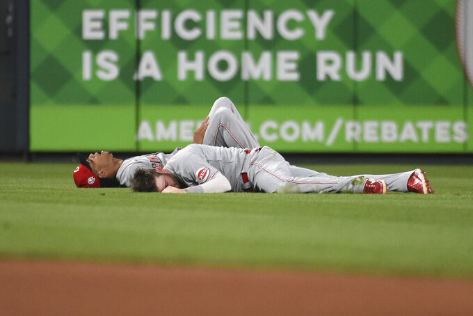 Cincinnati Reds center fielder Tyler Naquin and shortstop Jose Barrero lie on the grass after colliding during the sixth inning of a baseball game against the St. Louis Cardinals on Saturday, Sept. 11, 2021, in St. Louis. (AP Photo/Joe Puetz)