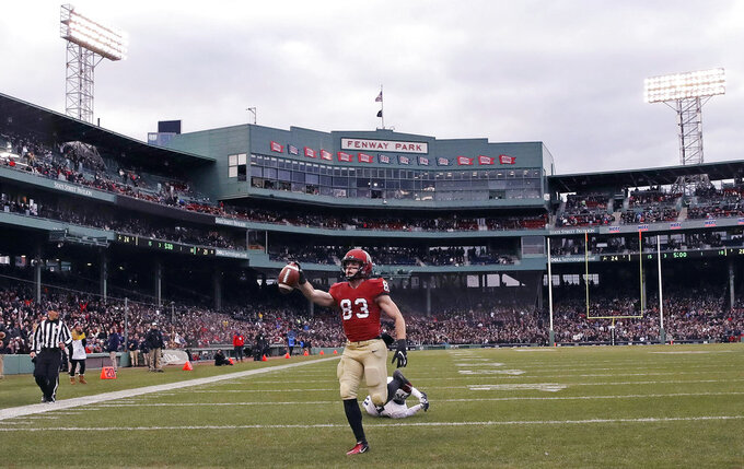 Harvard wide receiver Jack Cook (83) raises the ball after crossing the goal line for a touchdown against Yale during the second half of an NCAA college football game at Fenway Park in Boston, Saturday, Nov. 17, 2018. (AP Photo/Charles Krupa)